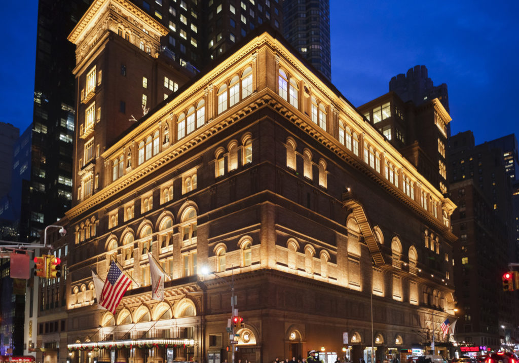 New York, New York, USA - December 11, 2015: Carnegie Hall in Manhattan in the evening. Located on the corner of 57th St. and 7th Ave., Carnegie Hall is one of the most well known concert halls in the world. People and vehicles can be seen.