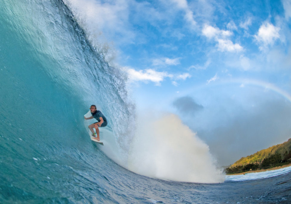 A professional surfer rides a perfect North Shore barrel with a rainbow in the background