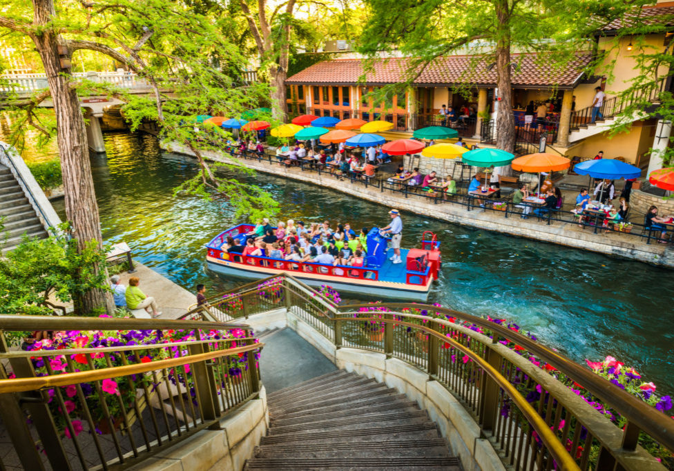San Antonio, Texas, USA - April 14, 2013: Tourists riding in tour boat and eating at restaurants along The Riverwalk in San Antonio Texas. The San Antonio Riverwalk is a world-famous park and walkway along the scenic canal of the San Antonio River, in downtown San Antonio Texas.