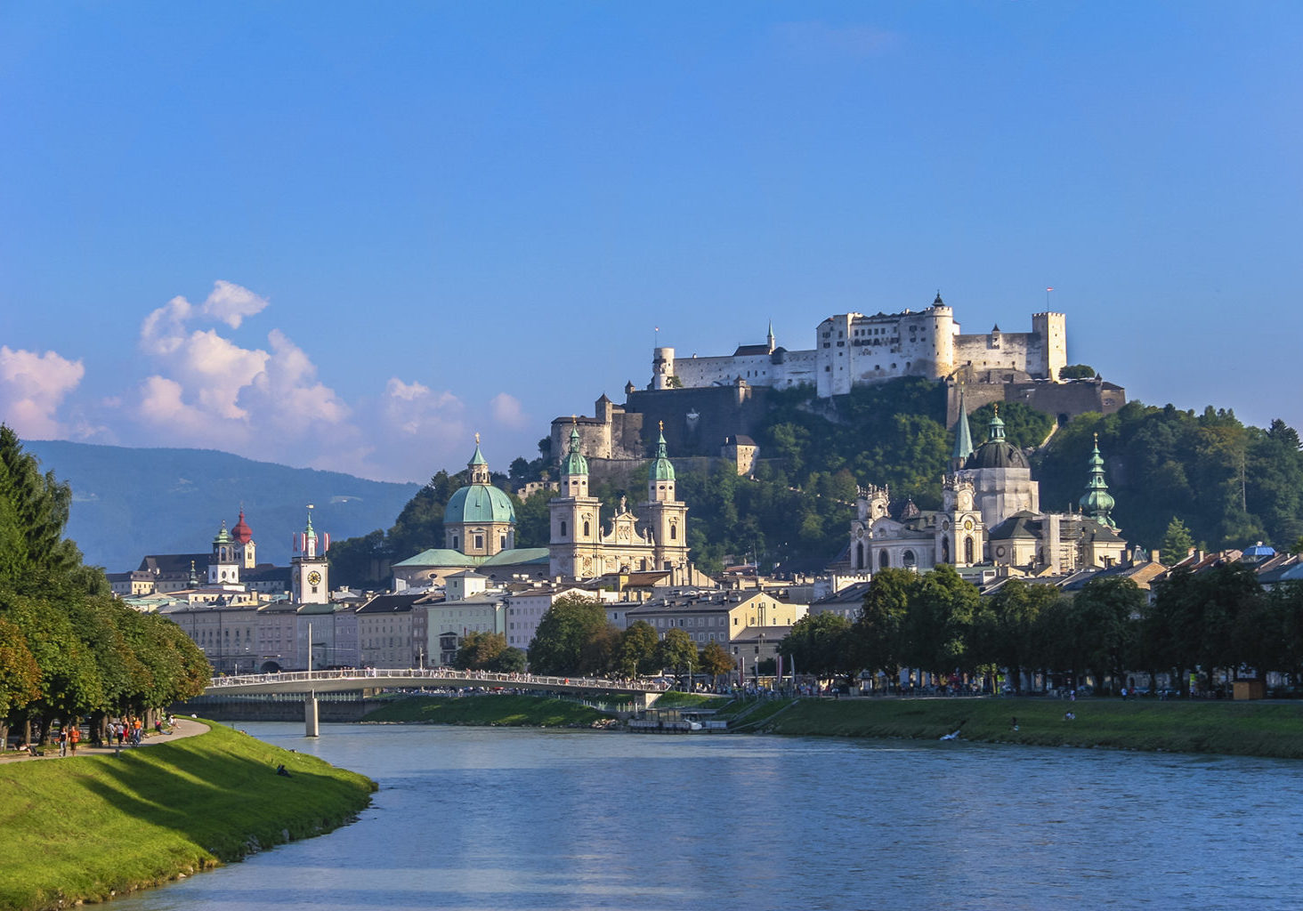 Salzburg in summer seen from one of the bridges on River Salzach. On the top of the rocky hill stands the imposing Hohensalzburg Fortress, built in 1077. The city is renowned for its baroque architecture and has been listed in UNESCO World Heritage Site in 1996. Salzburg, Austria.